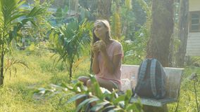 Young woman sitting on the bench at asian countryside village and eating snack. Backpacker traveler relax on trekking through local ethnic village stock video footage