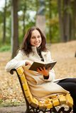 Young woman sitting on bench in autumn Stock Photos