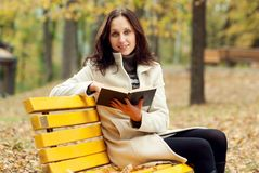 Young woman sitting on bench in autumn park Royalty Free Stock Photo