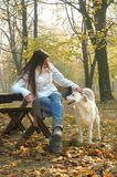 Young woman sitting on bench in autumn park cuddling dog Stock Photos