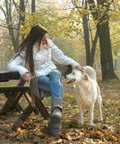 Young woman sitting on bench in autumn park cuddling dog Stock Photo