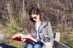 Young woman sitting on a bench in the  autumn park with her dog Royalty Free Stock Photo
