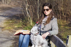 Young woman sitting on a bench in the  autumn park with her dog Royalty Free Stock Image