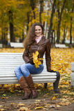 Young woman sitting on bench in the autumn park Stock Photo