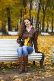Young woman sitting on bench in the autumn park Stock Photography
