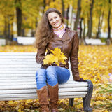 Young woman sitting on bench in the autumn park Royalty Free Stock Photography