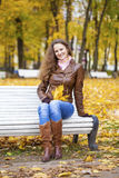 Young woman sitting on bench in the autumn park Stock Images