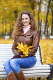 Young woman sitting on bench in the autumn park Royalty Free Stock Image