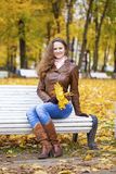 Young woman sitting on bench in the autumn park Stock Photos