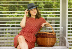 Young woman sitting on bench with basket Royalty Free Stock Images