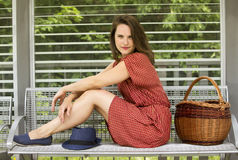Young woman sitting on bench with basket Stock Photos