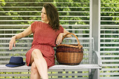 Young woman sitting on bench with basket Stock Image