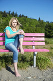 Young Woman Sitting On Bench At Beach Royalty Free Stock Image