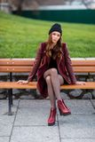 Young woman sitting on a bench. Stock Photo
