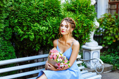 Young woman sitting on a bench with a bouquet of flowers Royalty Free Stock Photos