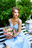 Young woman sitting on a bench with a bouquet of flowers Royalty Free Stock Photography