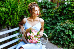 Young woman sitting on a bench with a bouquet of flowers Royalty Free Stock Image