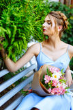 Young woman sitting on a bench with a bouquet of flowers Royalty Free Stock Photo