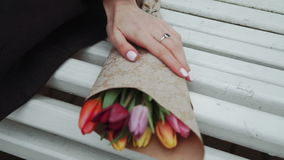 Young woman sitting on bench bouquet of flowers tulips in hand close-up, cold weather, white stock video