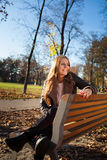 Young woman sitting on a bench in the city park in autumn/winter Royalty Free Stock Image