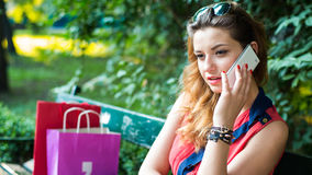 Young  woman sitting on a bench with colorful shopping bags and mobile phone. Stock Image
