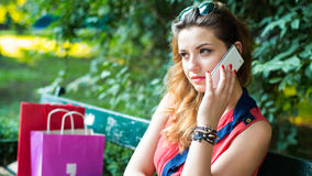 Young  woman sitting on a bench with colorful shopping bags and mobile phone. Royalty Free Stock Photography