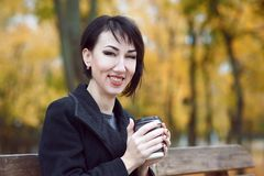 Young woman sitting on a bench and drinking coffee, autumn season, city park, yellow leaves stock images