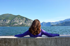 Young woman sitting on bench facing the lake Royalty Free Stock Photography