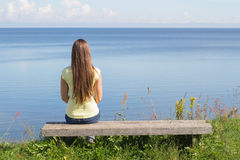 Young woman sitting on bench. Facing the sea Royalty Free Stock Photography