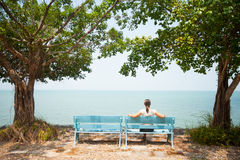 Young woman sitting on bench facing the sea Royalty Free Stock Photo