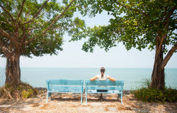 Young woman sitting on bench facing the sea Royalty Free Stock Photography