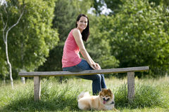 A young woman sitting on a bench, with her dog stock photos