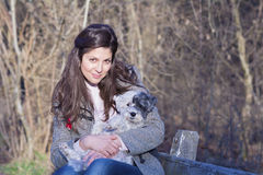 Young woman sitting on a bench hugging her dog Stock Image