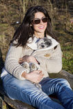 Young woman sitting on a bench hugging her dog Royalty Free Stock Photography