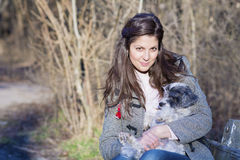 Young woman sitting on a bench hugging her dog Royalty Free Stock Photos