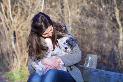 Young woman sitting on a bench hugging her dog. Brunette woman sitting on a bench in the autumn park hugging her white dog Royalty Free Stock Photo