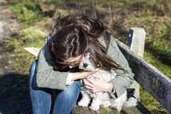 Young woman sitting on a bench hugging her white  dog Royalty Free Stock Photos