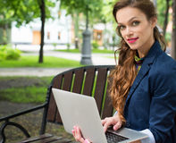 Young Woman Sitting on the Bench with Laptop Stock Photo