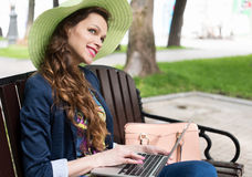 Young Woman Sitting on the Bench with Laptop Royalty Free Stock Photography