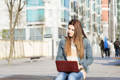Young woman sitting on bench and laptop computer. Stock Photos