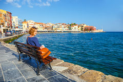 Young woman sitting on the  bench and looking at old port in Chania Stock Image