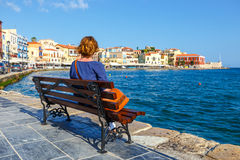 Young woman sitting on the  bench and looking at old port in Chania Royalty Free Stock Photos
