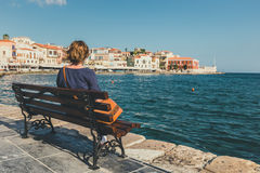 Young woman sitting on the  bench and looking at old port in Chania Royalty Free Stock Images