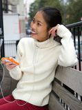 Young woman sitting on bench with mobile phone and earphones Stock Photos