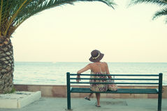 Young woman sitting on a bench near the sea Stock Images