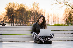Young woman sitting on a bench, near the university, working with laptop. Portrait of beautiful smiling dark-haired young woman, against summer green park Royalty Free Stock Photography