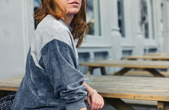 Young woman sitting on bench outside pub Royalty Free Stock Image