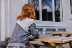 Young woman sitting on bench outside pub Royalty Free Stock Images