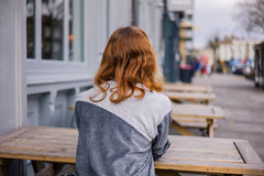 Young woman sitting on bench outside pub Stock Photos