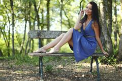 Young woman sitting on the bench in park Royalty Free Stock Photography